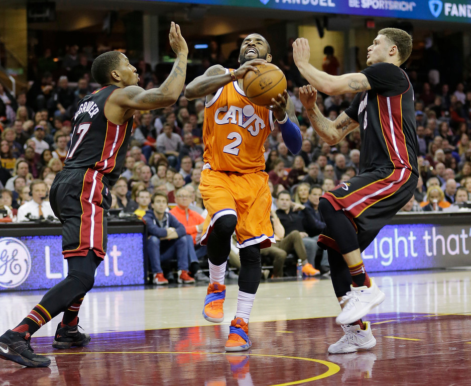 . Cleveland Cavaliers\' Kyrie Irving, center, drives past Miami Heat\'s Rodney McGruder, left, and Tyler Johnson in the first half of an NBA basketball game Friday, Dec. 9, 2016, in Cleveland. (AP Photo/Tony Dejak)