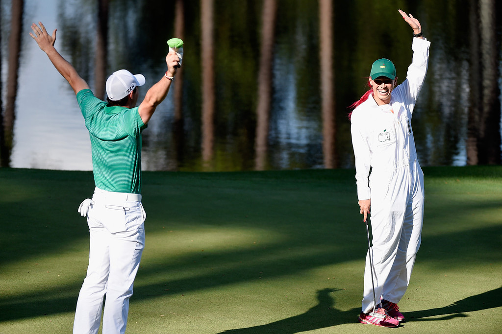 . Rory McIlroy of Northern Ireland celebrates as his caddie/girlfriend Caroline Wozniacki makes a birdie putt on the ninth green during the 2014 Par 3 Contest prior to the start of the 2014 Masters Tournament at Augusta National Golf Club on April 9, 2014 in Augusta, Georgia.  (Photo by Harry How/Getty Images)