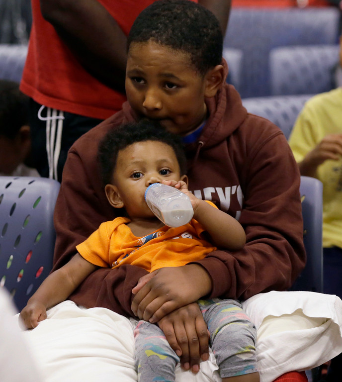 . Evacuee Edward Jones, 11, holds his step-brother Mickel Duane Batts at the Lakewood Church in Houston, Tuesday, Aug. 29, 2017. Joel Olsten and his congregation have set up their church as a shelter for evacuees from the flooding by Tropical Storm Harvey. (AP Photo/LM Otero)
