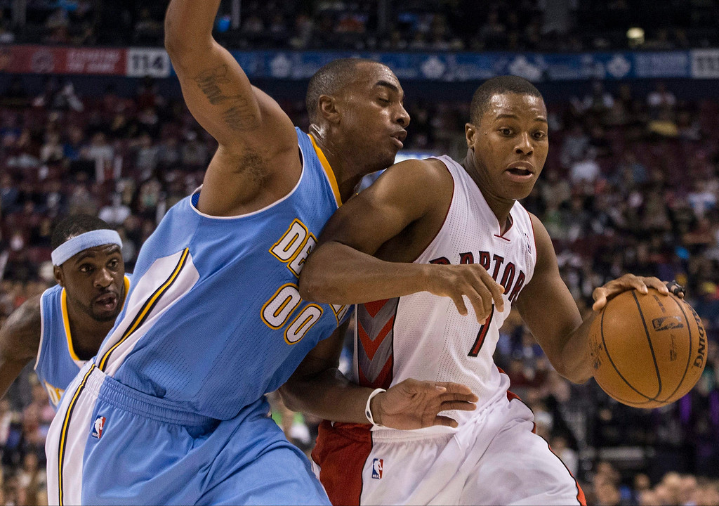 . Toronto Raptors\' Kyle Lowry, right, drives at Denver Nuggets\' Darrell Arthur during the second half of an NBA basketball game on Sunday, Dec. 1, 2013, in Toronto. (AP Photo/The Canadian Press, Chris Young)