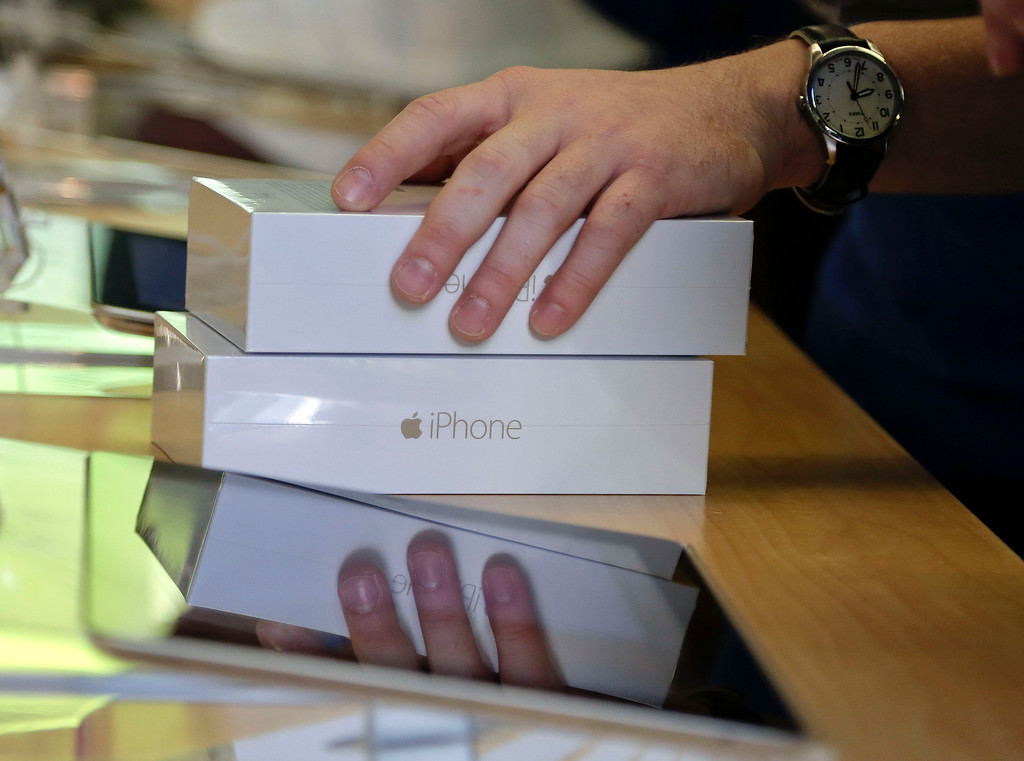 . An Apple store employee checks out a customer who bought two iPhone 6s, Friday, Sept. 19, 2014,  in New York. The highly anticipated iPhone 6 and iPhone 6 Plus are being released in stores today. (AP Photo/Julie Jacobson)