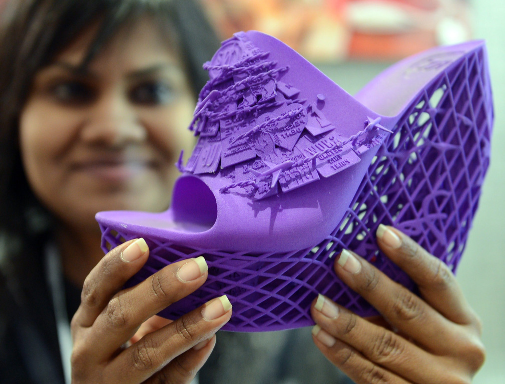 . A stand assistant holds a shoe printed with a 3D printer at the Consumer Electronics Show (CES) 2014 in Las Vegas, USA, 08 January 2014. The fair runs from 07 to 10 January 2014. This new way of printing objects can create anything from guns to doorknobs to replacement parts for a dishwasher. The technology is getting closer to mass market appeal as it becomes cheaper. Reports state online retailers are eying a world where people shop on the internet and then print out their purchases at home.  EPA/BRITTA PEDERSEN