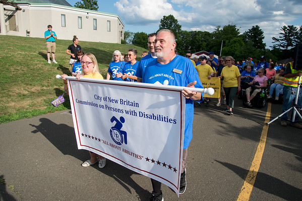 07/24/19 Wesley Bunnell   Staff Commissioner Alicia Rutkowski, L, and Commissioner Alden Russell, R, carry a banner at the start of the Walk and Roll on Wednesday afternoon at Walnut Hill Park. The Walk and Roll is hosted by the citys Commission on Persons with Disabilities and celebrates the signing of the American with Disabilities Act of 1990 and serves to raise awareness for improving the quality of life for all residents in the city, regardless of disability.