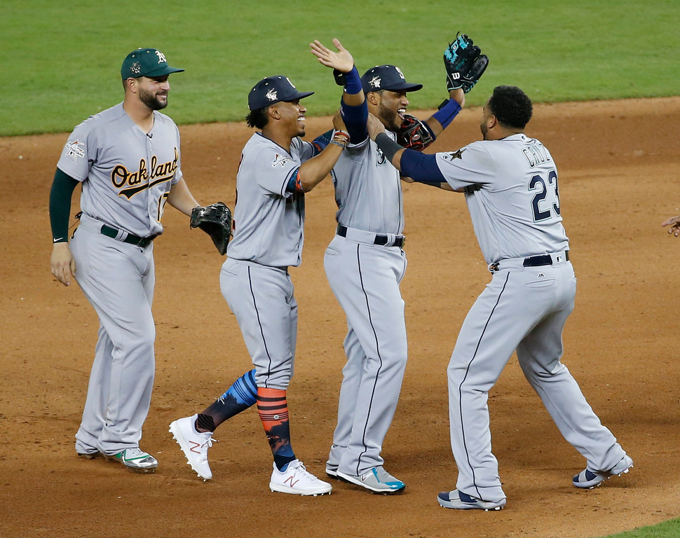 . American League teammates celebrate winning the MLB baseball All-Star Game, Tuesday, July 11, 2017, in Miami. The American League defeated the National League 2-1 in ten innings. Seattle Mariners Robinson Cano (22), second from right, hit the game winning home run. (AP Photo/Wilfredo Lee)