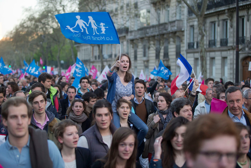""". Anti gay marriage activists wavs a flag with the logo of the movement on it during a rally to protest against the new law after French lawmakers legalized same-sex marriage, Tuesday, April 23, 2013 in Paris. Lawmakers legalized same-sex marriage after months of bruising debate and street protests that brought hundreds of thousands to Paris. Tuesday\'s 331-225 vote came in the Socialist majority National Assembly. France\'s justice minister, Christiane Taubira, said the first weddings could be as soon as June. Flags read, \""""demonstration for all.\"""" (AP Photo/Michel Euler)"""