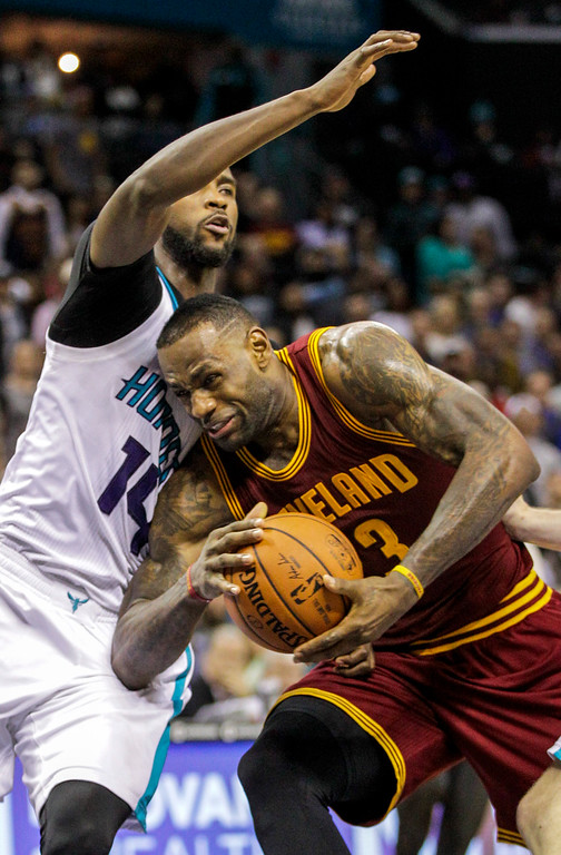 . Cleveland Cavaliers forward LeBron James, right, drives into Charlotte Hornets forward Michael Kidd-Gilchrist during the second half of an NBA basketball game Wednesday, Feb. 3, 2016, in Charlotte, N.C. Charlotte won 106-97. (AP Photo/Nell Redmond)