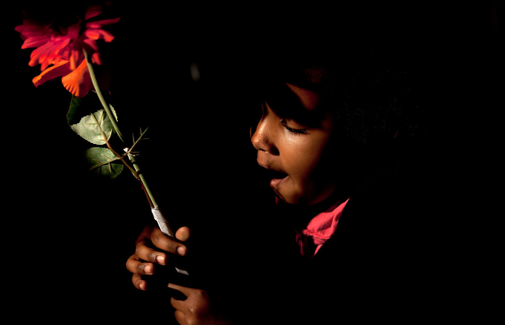 . A child from a community group from Pretoria holds flowers and sings religious songs to show  appreciation and support for former South African President Nelson Mandela, on the street outside the Mediclinic Heart Hospital where he is being treated in Pretoria, South Africa Tuesday, June 25, 2013. South Africa\'s president Jacob Zuma on Tuesday urged his compatriots to show their appreciation for Nelson Mandela, who is in critical condition in a hospital, by marking his 95th birthday next month with acts of goodness that honor the legacy of the anti-apartheid leader. (AP Photo/Ben Curtis)