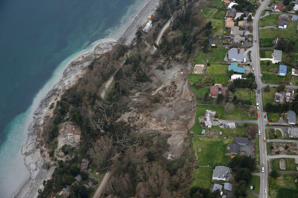 . In this aerial photo, a landslide is shown near Coupeville, Wash. on Whidbey Island, Wednesday, March 27, 2013.   Whidbey Island authorities say one home has been severely damaged by the landslide that has isolated or threatened 33 more homes in the community overlooking Puget Sound about 50 miles north of Seattle.   Central Whidbey Fire and Rescue evacuated one person from the damaged home. About 10 more residents have been evacuated by boat.  (AP Photo/Ted S. Warren)