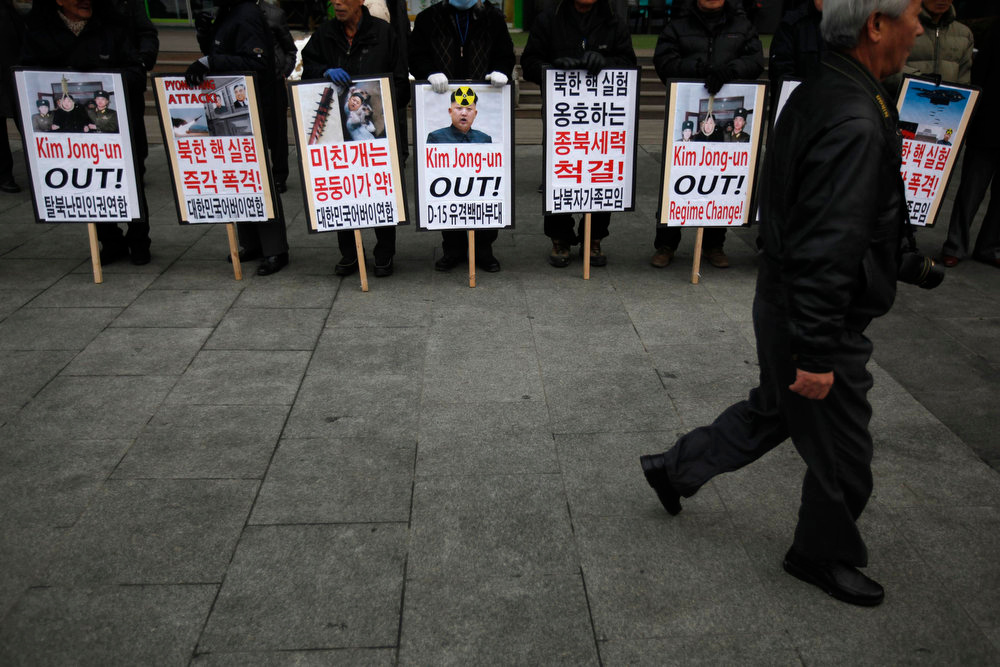 ". An activist from anti-North Korea civic group walks past banners bearing messages to denounce North Korea during a rally against North Korea\'s nuclear test  near the U.S. embassy in central Seoul February 12, 2013. North Korea conducted its third-ever nuclear test on Tuesday, a move likely to anger its main ally China and increase international action against Pyongyang and its new young leader, Kim Jong-un. U.N. Secretary-General Ban Ki-moon condemned North Korea\'s test, saying it was a ""clear and grave violation\"" of U.N. Security Council resolutions.   REUTERS/Kim Hong-Ji"