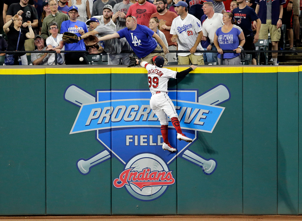. Cleveland Indians\' Daniel Robertson jumps at the wall but cannot catch a home run hit by Los Angeles Dodgers\' Cody Bellinger during the eighth inning of a baseball game, Tuesday, June 13, 2017, in Cleveland. (AP Photo/Tony Dejak)