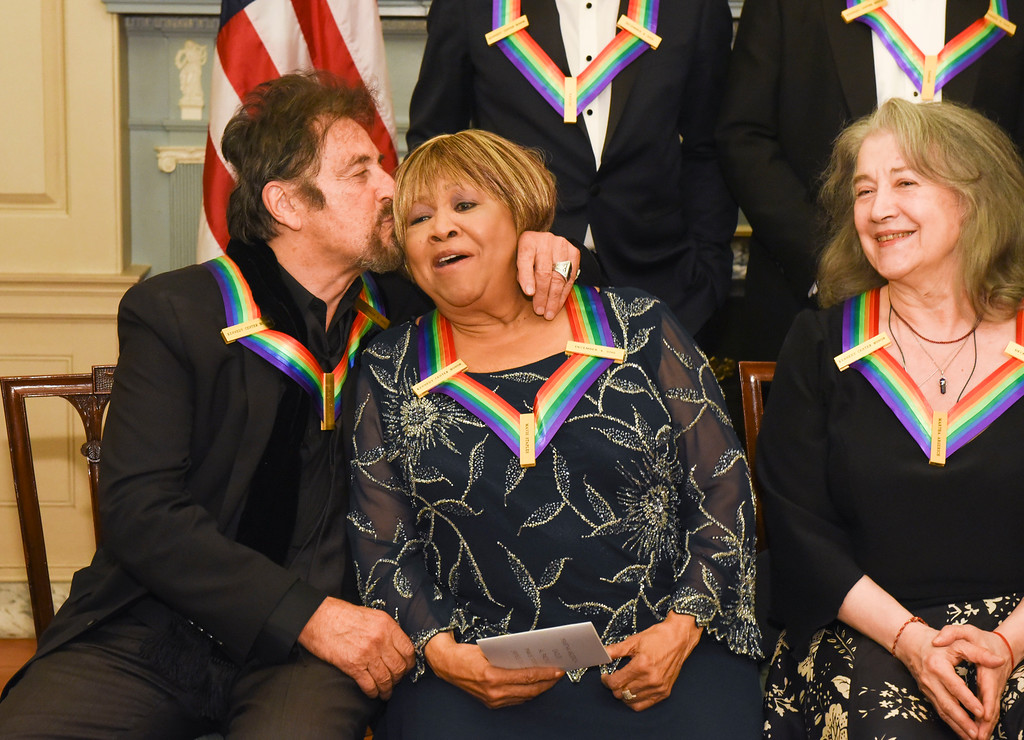 . Kennedy Center Honorees Al Pacino kisses fellow honoree Mavis Staples, center, with honoree Martha Argerich, right, following the State Department for the Kennedy Center Honors gala dinner, Saturday, Dec. 3, 2016, in Washington. (AP Photo/Kevin Wolf)