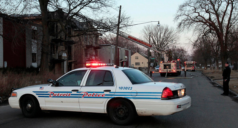 . A Detroit Police vehicle blocks a street from traffic as firefighters pour water on a smouldering vacant apartment building that burned earlier in the day on the east side of Detroit, Michigan March 23, 2013.  When the state-imposed manager of Detroit, Kevyn Orr, begins the job on Monday he will wade into a city of crumbling neighborhoods where police fail to respond to some calls, arson fires burn out of control, and residents scour charred buildings for scrap metal to sell. March 23, 2013. REUTERS/ Rebecca Cook