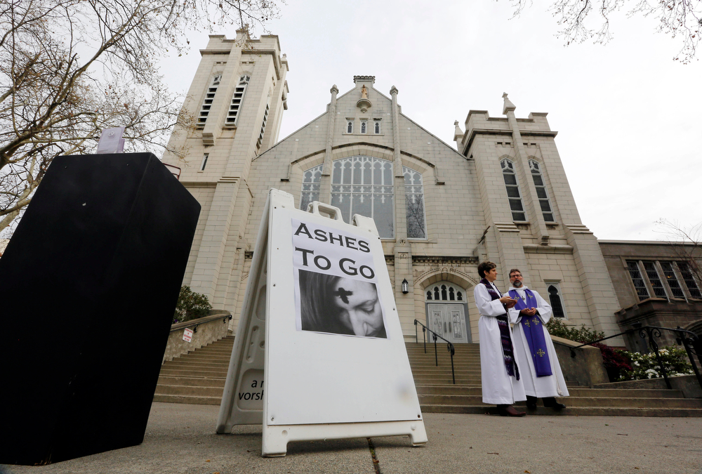 . Associate Pastor Leslie Welton, left, and Pastor Frank Espegren wait outside St. John\'s Lutheran Church, in Sacramento, Calif.,  to provide Ashes To Go for those who want to participate in the start of the Christian observance of Lent but are unable to attend a full church service Wednesday March 5,  2014.   Ash Wednesday marks the beginning of the Lenten season, a time when Christians commit to acts of penitence and prayer in preparation for Easter Sunday.(AP Photo/Rich Pedroncelli)