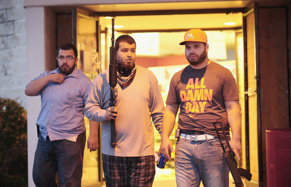 . FERGUSON, MO - AUGUST 16:  Business owners carry assault weapons to protect their grocery store after another night of rioting and looting following protests over the shooting death of Michael Brown on August 16, 2014 in Ferguson, Missouri. Looters ransacked several businesses for several hours as police held a position nearby with military grade weapons and armored personnel carriers (APC). Violent outbreaks have taken place almost nightly in Ferguson since the shooting death of Brown by a Ferguson police officer on August 9.  (Photo by Scott Olson/Getty Images)