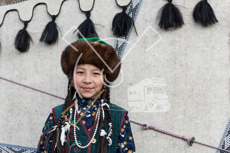 Cute kyrgyz girl wearing the traditional kyrgyz costume and a fur hat at the World Nomad Games 2018 yurt camp