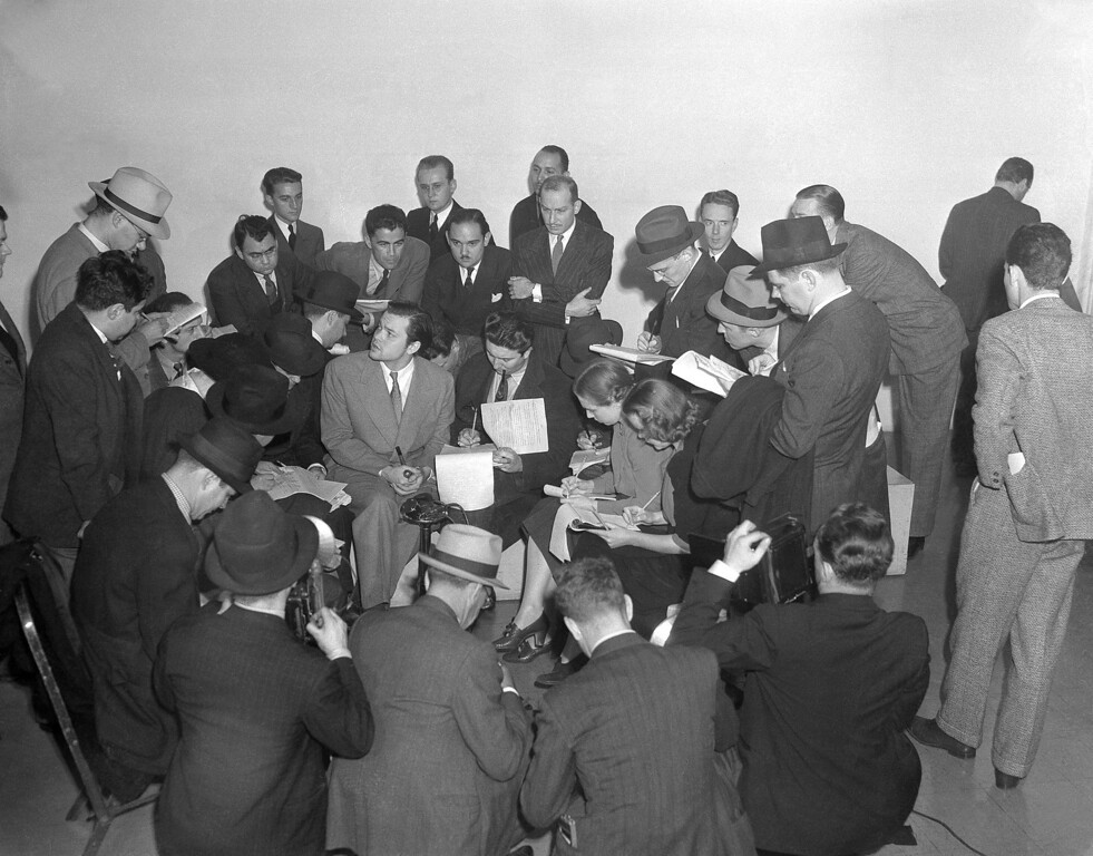 """. Orson Welles, center, young director who presented the dramatization of H.G. Wells\' \""""War of the Worlds\"""" in New York on Oct. 31, 1938, that caused great panic radio listeners. Amazed that his dramatization had been so realistic, he expressed regret. (AP Photo/Charles Kenneth Lucas)"""
