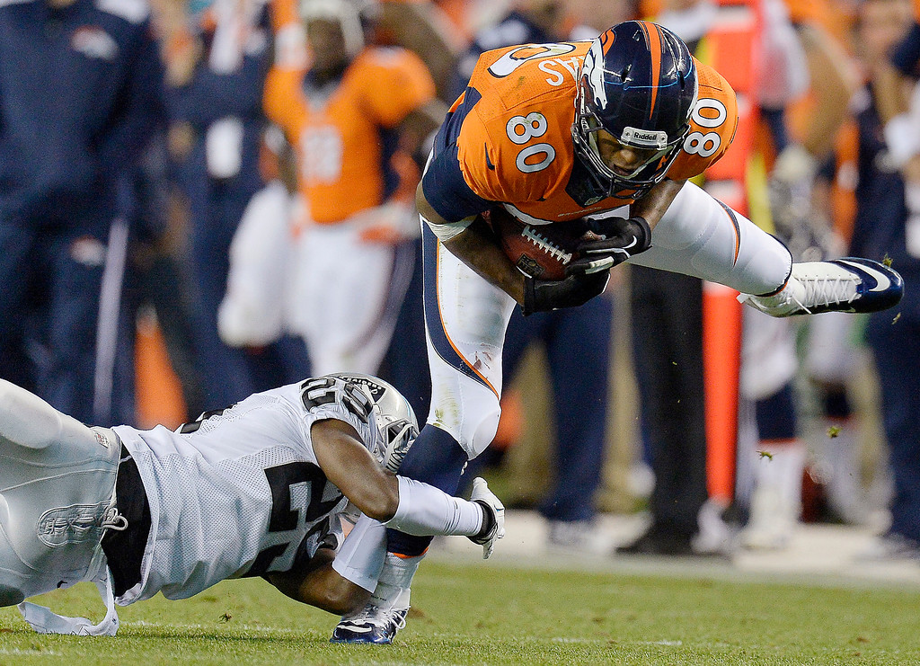 . Denver Broncos tight end Julius Thomas (80) eludes a tackle by Oakland Raiders cornerback Brandian Ross (29) in the first quarter in Denver.   (Photo by John Leyba/The Denver Post)