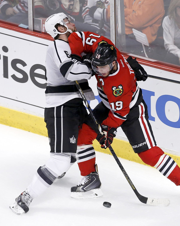 . Chicago Blackhawks center Jonathan Toews (19) battles Los Angeles Kings defenseman Jake Muzzin during the second period of Game 1 of the Western Conference finals in the NHL hockey Stanley Cup playoffs in Chicago on Sunday, May 18, 2014. (AP Photo/Charles Rex Arbogast)
