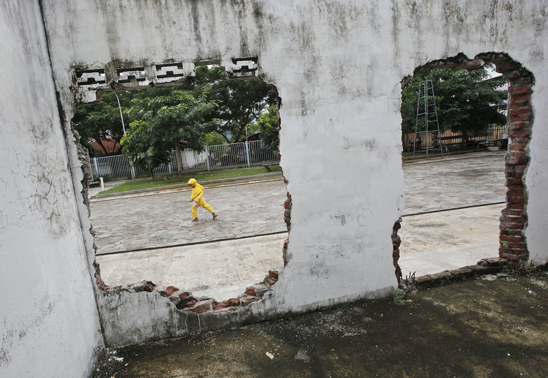 . An Acehnese girl plays near a house damaged by the Indian Ocean tsunami ten years ago, in Banda Aceh, Aceh province, Indonesia, Friday, Dec. 26, 2014. The devastating Boxing Day tsunami in 2004 struck a dozen countries around the Indian Ocean rim, killing 230,000 people, most of them in Aceh. (AP Photo/Binsar Bakkara)