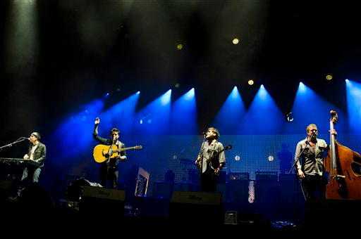 Description of . Mumford & Sons band members, from left, Ben Lovett, Marcus Mumford, Country Winston and Ted Dwane perform on Wednesday, Aug. 28, 2013 at the West Side Tennis Club in the Forest Hills neighborhood of the Queens borough of New York. (Photo by Charles Sykes/Invision/AP)