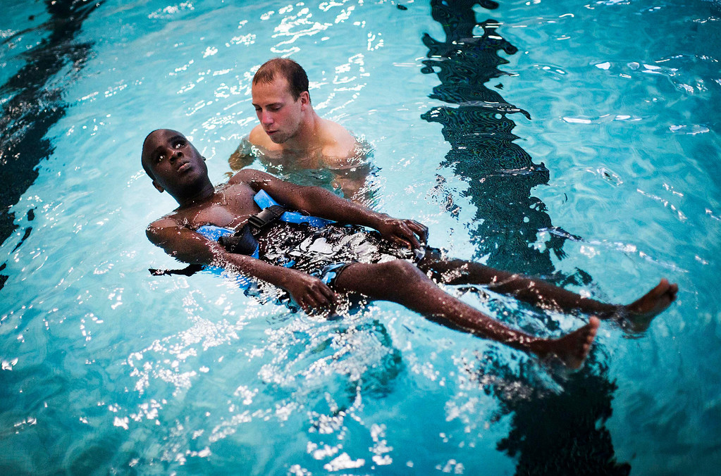 . Ahmat Djouma learns to float in the pool with his counselor Adam Dwyer at Camp Abilities in Brockport, New York, June 26, 2013. Camp Abilities is a not-for-profit week-long developmental camp using sports to foster greater independence and confidence in children who are blind, visually impaired, and deaf-blind. Photo taken June 26, 2013.       REUTERS/Mark Blinch