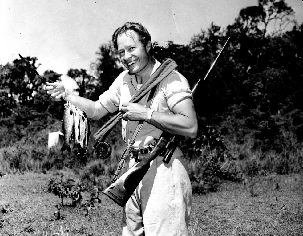 . MAR 12 1950  Trout fishing on Mt. Kenya differs little from that in Colorado, Michigan Pennsylvania or any other U. S. state except that a high-power rifle is a comforting adjunct along the fishing streams where rhinos and buffalos often come to drink. Here Wallace Taber, Denver Post out­door columnist, displays both fish and rifle.  Credit: Denver Post