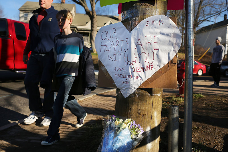 Description of . Flowers and signs of sympathy adorn the street leading to the Sandy Hook School oon December 15, 2012 in Newtown, Connecticut. Twenty six people were shot dead, including twenty children, after a gunman identified as Adam Lanza opened fire at Sandy Hook Elementary School. Lanza also reportedly had committed suicide at the scene. A 28th person, believed to be Nancy Lanza was found dead in a house in town, was also believed to have been shot by Adam Lanza.  (Photo by Spencer Platt/Getty Images)