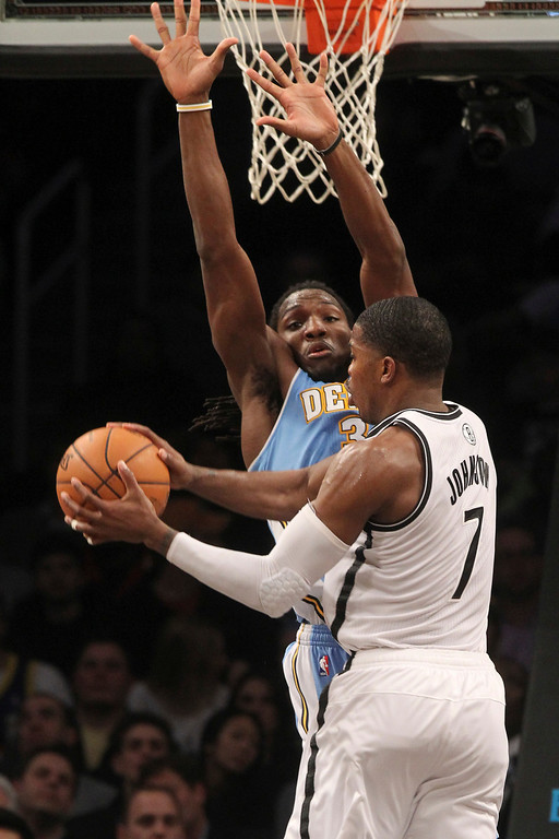. Brooklyn Nets\' Joe Johnson (7) goes up against Denver Nuggets\' Ty Lawson during the second half of an NBA basketball game on Wednesday, Feb. 13, 2013, at Barclays Center in New York. The Nuggets won 119-108. (AP Photo/Mary Altaffer)