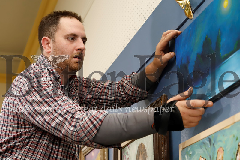 Butler Arts Center gallery director Stephen Haley adjusts a newly hung painting Tuesday. Volunteers and gallery staff spent the evening preparing for the gallery's latest exhibit set to open Friday and feature a number of local artists.  Seb Foltz/Butler Eagle
