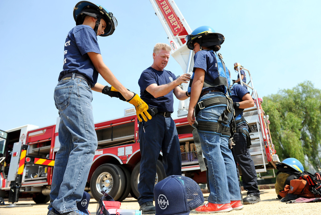 . (John Valenzuela/Staff Photographer) Redlands Fire Capt. Mike Howard assist Redlands Emergency Services Academy student with her climbing harness during R.E.S.A ladder training at the University of Redlands, Thursday, July 18, 2013.