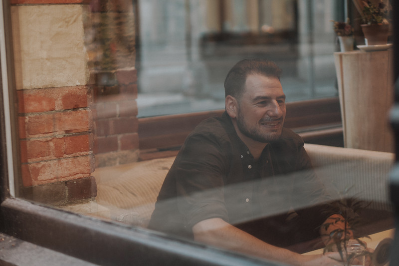 A man smiles inside a cafe as he looks across a table while holding a glass.