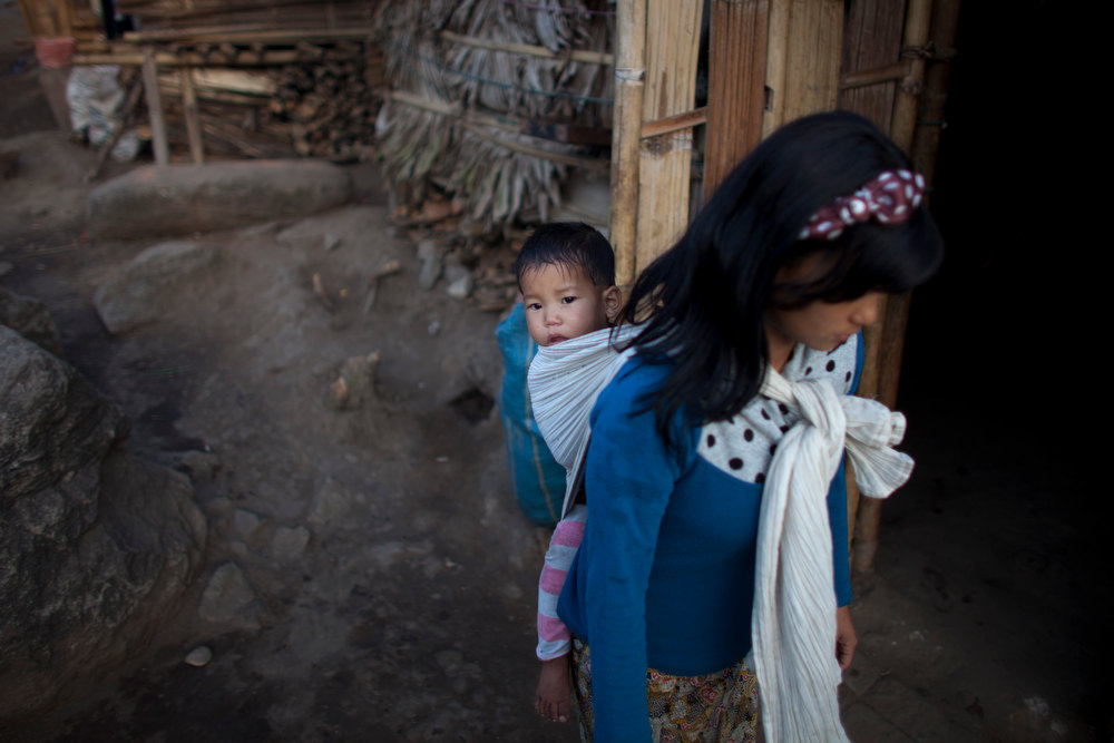. A woman carries a child on her back at an Internally Displaced Persons refuge camp set up at a land of Woichyai Baptist Church in the town of Laiza, in northern Myanmar\'s Kachin-controled region, Tuesday, Jan. 29, 2013. (AP Photo/Alexander F. Yuan)