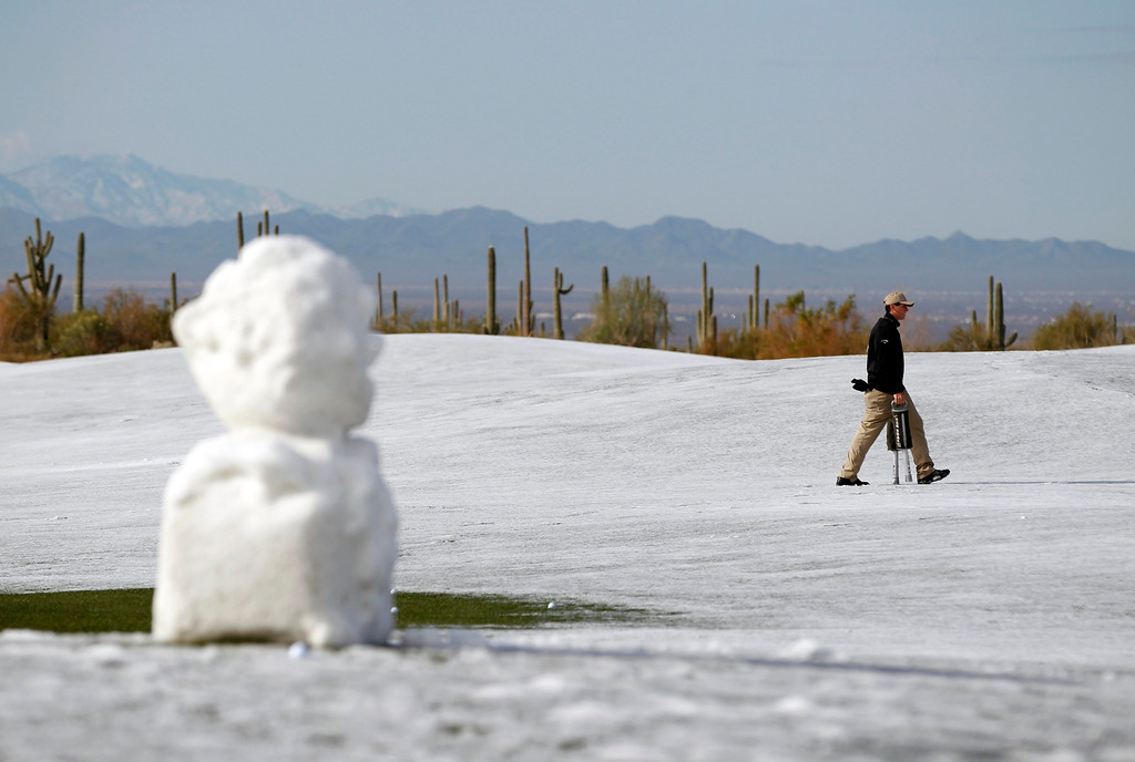 . A course worker picks up golf balls on the driving range as snow and ice continues to delay first round play of the WGC-Accenture Match Play Championship golf tournament in Marana, Arizona February 21, 2013. REUTERS/Matt Sullivan