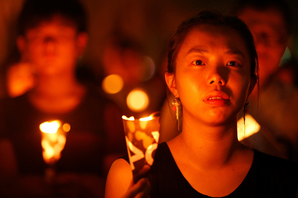 . A woman holds a candle as she she joins tens of thousands of people attending a candlelight vigil at Victoria Park in Hong Kong Wednesday, June 4, 2014 to mark the 25th anniversary of the June 4th Chinese military crackdown on the pro-democracy movement in Beijing. (AP Photo/Kin Cheung)
