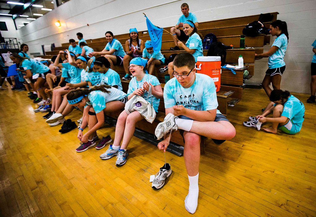 . Nicholas Walker ties his shoes after participating in judo at Camp Abilities in Brockport, New York, June 25, 2013.  Camp Abilities is a not-for-profit week-long developmental camp using sports to foster greater independence and confidence in children who are blind, visually impaired, and deaf-blind. Photo taken June 25, 2013.     REUTERS/Mark Blinch