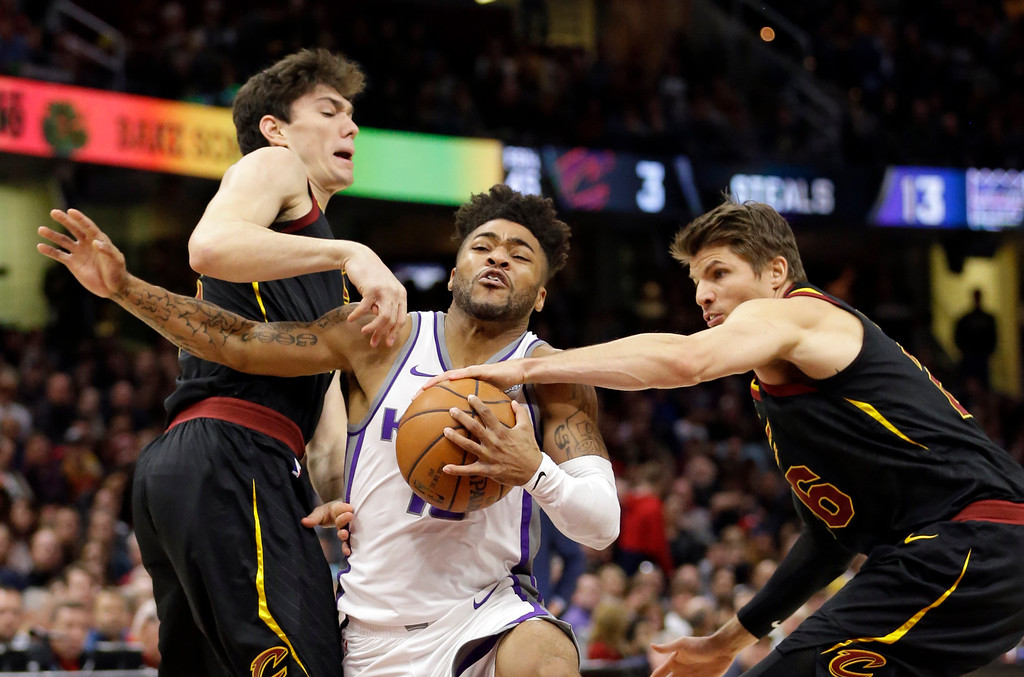 . Sacramento Kings\' Frank Mason III, center, drives between Cleveland Cavaliers\' Cedi Osman, left, from Turkey, and Kyle Korver in the second half of an NBA basketball game, Wednesday, Dec. 6, 2017, in Cleveland. The Cavaliers won 101-95. (AP Photo/Tony Dejak)
