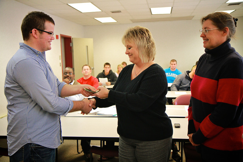 Business Classes present cash collected through class projects to United Way representatives.