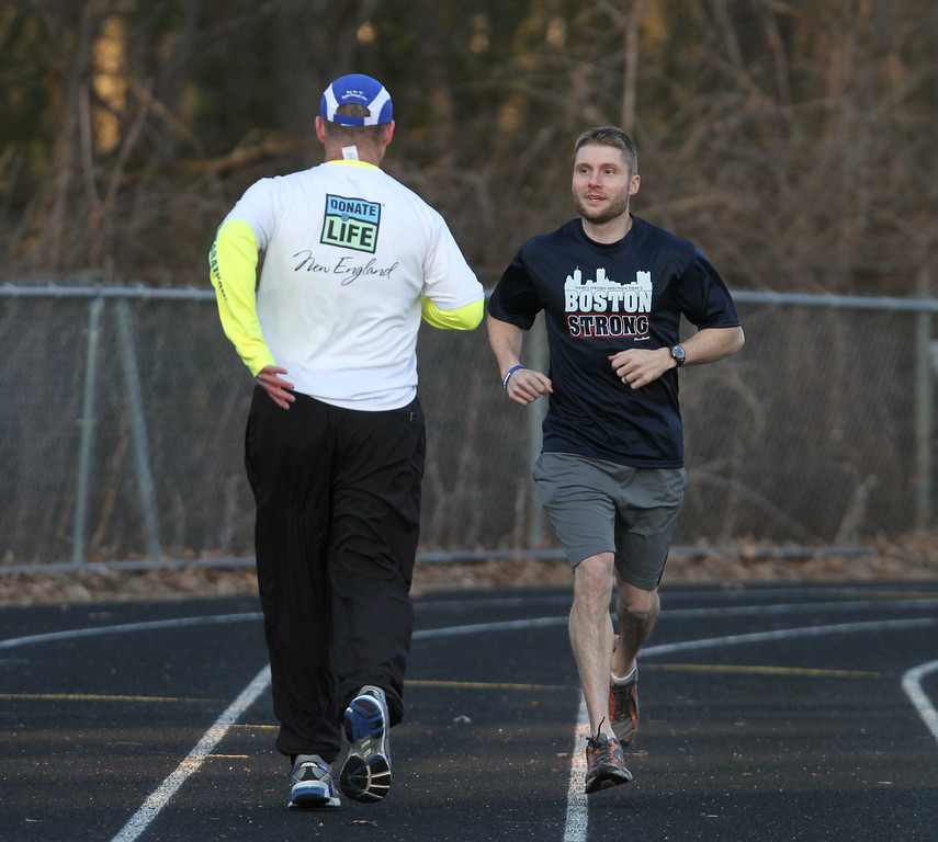 . Donald Davis, 54, of Reading, left, will run the Boston Marathon route Sunday a week early to raise money for DonateLife and promote organ and tissue donation. His nephew Bryon Patten, 34, of Woburn, right, will run with him forwards to keep him on course. Both are originally from Billerica. They are doing a run at the Marshall Middle School track to work on their pace. (SUN/Julia Malakie)
