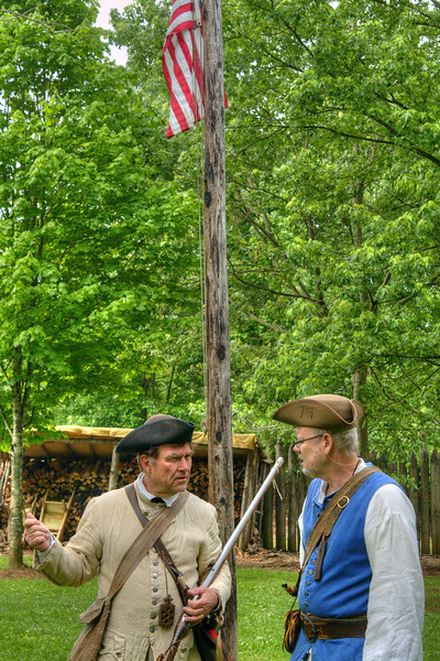 Two early settler reenactors talk inside the recreation of Fort Watauga during the Siege of Fort Watauga at Sycamore Shoals State Park in Elizabethton, VA on Saturday, May 17, 2014. Copyright 2014 Jason Barnette  The Siege of Fort Watauga is a two-day reenactment held each year at the recreation of the fort inside Sycamore Shoals State Historic Park. The reenactment brings in dozens of reenactors and hundreds of visitors as they tell the story of an attack on the early settlers village by Dragging Canoe, and how they successfully defended themselves. During the reenactment, the fort is open to the public with demonstrations of all areas of early settler life on the frontiers.