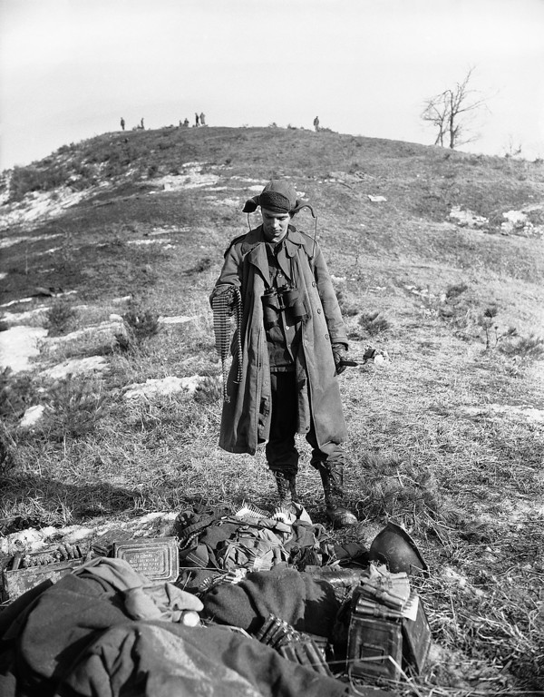 . Cpl. Robert M. Kessler of St. Louis, Mo., member of U.N. forces which fought bitter battle with Reds in Chipyong sector of Korea on Feb. 24, 1951, examines Chinese machine gun belt and other ammunition and gear lying on ground. (AP Photo/E.N. Johnson )