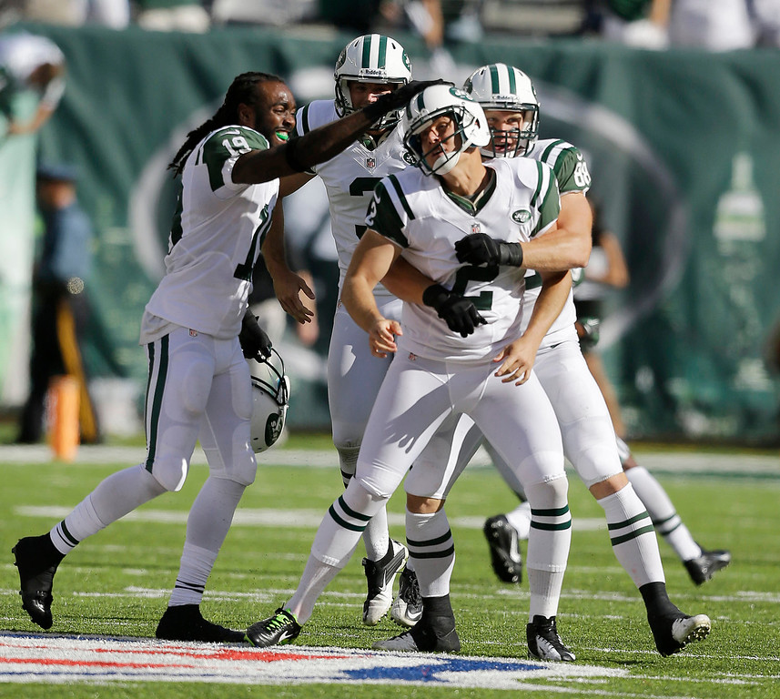 . New York Jets kicker Nick Folk (2) is congratulated by teammates on his 48-yard field goal against the Tampa Bay Buccaneers in the closing seconds of an NFL football game, Sunday, Sept. 8, 2013, in East Rutherford, N.J. The Jets won 18-17. (AP Photo/Mel Evans)