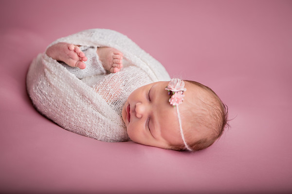 Colour studio newborn photograph of baby girl wrapped in white on a pink backdrop with a pink floral headband
