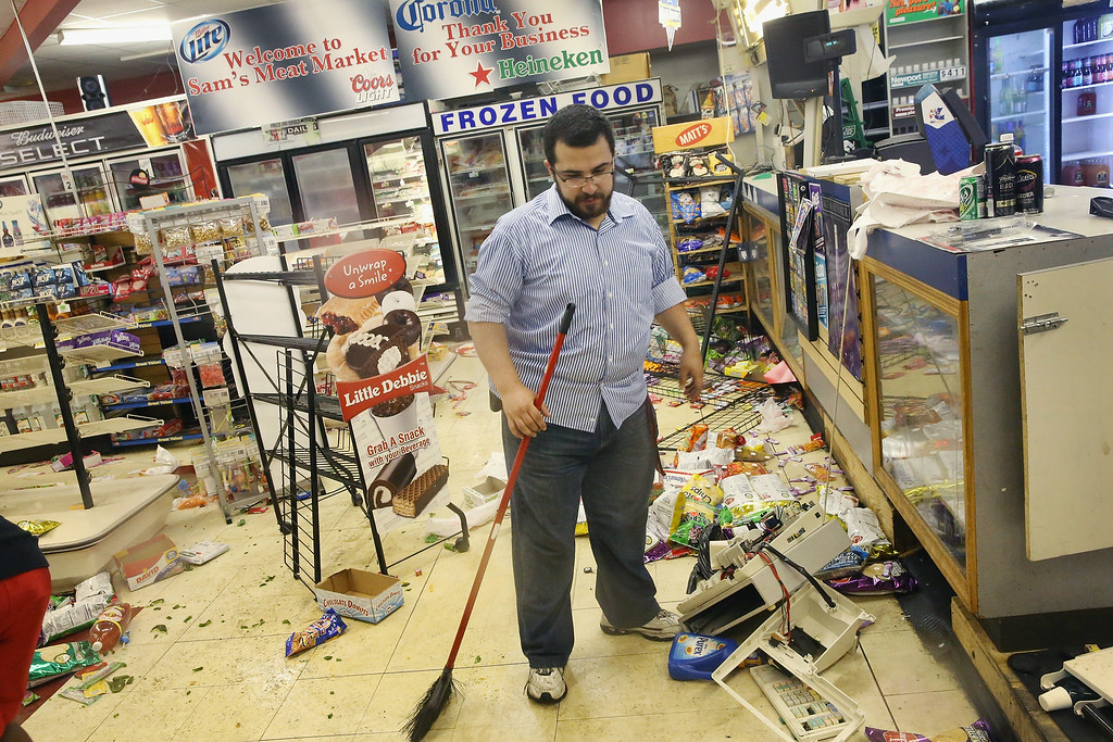 . FERGUSON, MO - AUGUST 16:  Business owner Mustafa Alshalabi cleans damage to his store, Sam\'s Meat Market, after it was looted during another night of rioting following protests over the shooting death of Michael Brown on August 16, 2014 in Ferguson, Missouri. Alshalabi is carrying a firearm on his side in order to protect his property. Looters ransacked several businesses for several hours as police held a position nearby with military grade weapons and armored personnel carriers (APC). Violent outbreaks have taken place almost nightly in Ferguson since the shooting death of Brown by a Ferguson police officer on August 9.  (Photo by Scott Olson/Getty Images) *** BESTPIX ***