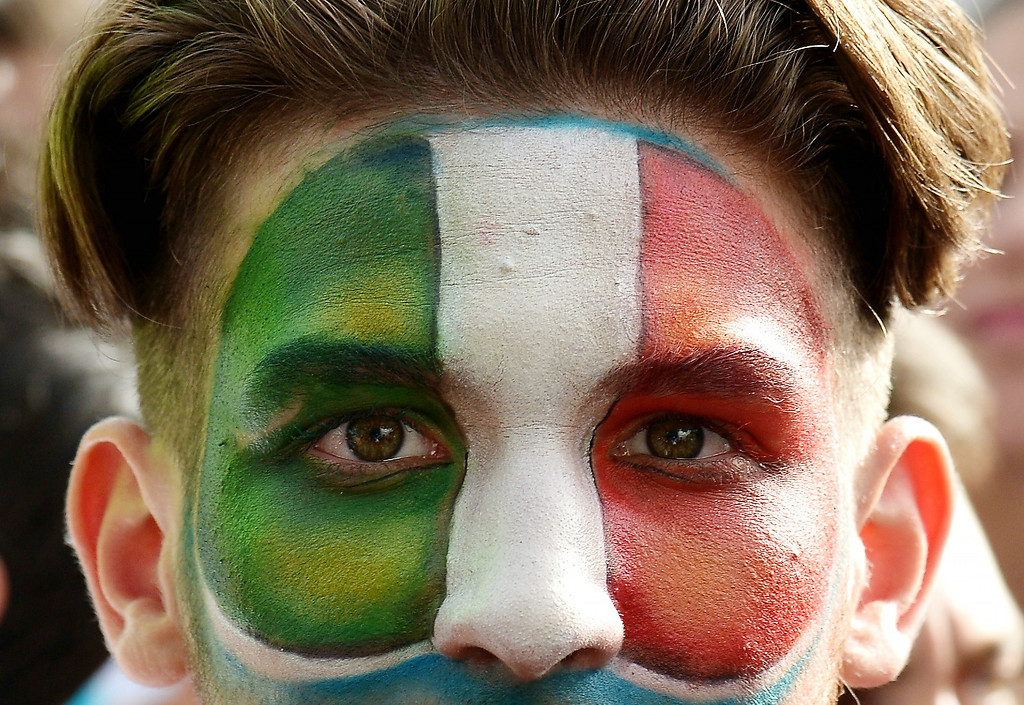 . An Italy fan with his face painted in the colors of the Italian flag watches the FIFA World Cup 2014 Group D football match Italy vs Uruguay on a giant screen in central Rome on June 24 , 2014.   ALBERTO PIZZOLI/AFP/Getty Images
