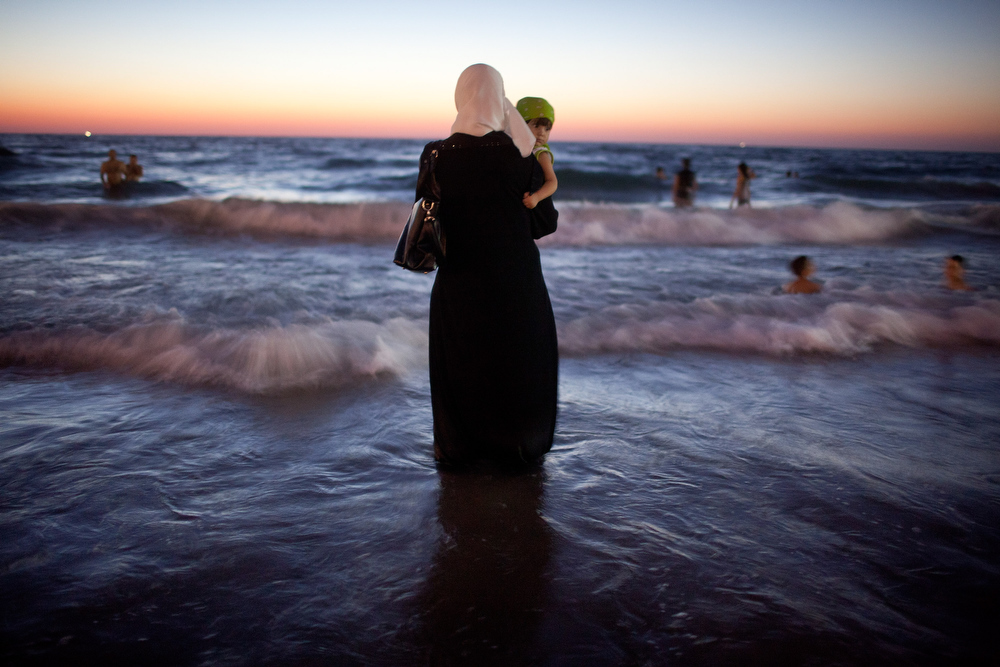 Description of . A woman holds her baby as Palestinians enjoy a day at a beach during Eid al-Fitr, which marks the end of the holy month of Ramadan on August 21, 2012 in Tel Aviv, Israel. According to the Israel's coordinator for government activities in the territories, Israel has allowed the entry of over 1 million Palestinians from the occupied West Bank since the beginning of Ramadan due to improved security.   (Photo by Uriel Sinai/Getty Images)