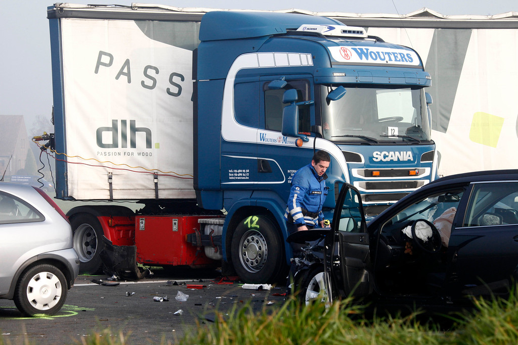 . A Belgian gendarme stands at the scene of a pileup involving dozens of cars and trucks near Zonnebeke, Belgium, Tuesday, Dec. 3, 2013. (AP Photo / Michel Spingler)
