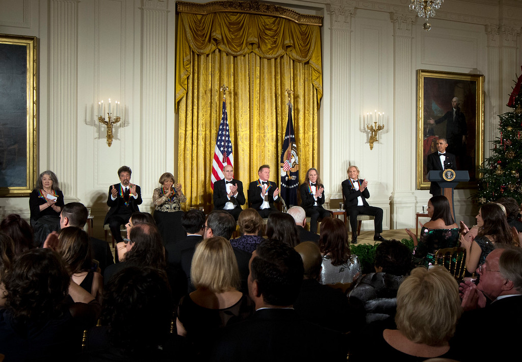 . President Barack Obama, right, is applauded by the recipients of the 2016 Kennedy Center Honors, from left, Argentine pianist Martha Argerich, actor Al Pacino, gospel and blues singer Mavis Staples, musician James Taylor, and members of the rock band the Eagles, Don Henley, Timothy Schmit, and Joe Walsh, during a reception in their honor in the East Room of the White House in Washington, Sunday, Dec. 4, 2016, hosted by the president and first lady Michelle Obama. (AP Photo/Manuel Balce Ceneta)