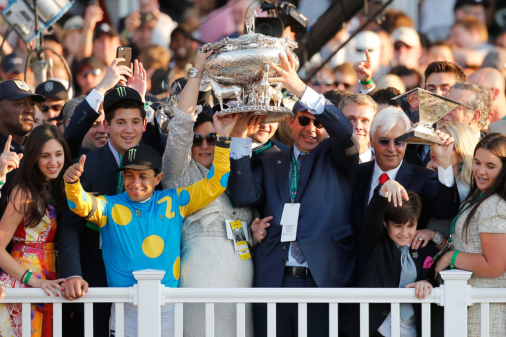 . Victor Espinoza (L), jockey of American Pharoah #5, owner of Ahmed Zayat, and trainer Bob Baffert (R), celebrate with the Belmont Stakes and Triple Crown Trophies after winning the 147th running of the Belmont Stakes at Belmont Park on June 6, 2015 in Elmont, New York. With the wins American Pharoah becomes the first horse to win the Triple Crown in 37 years  (Photo by Rob Carr/Getty Images)