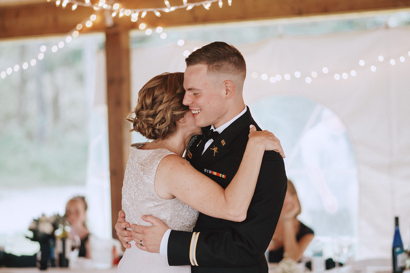 The groom smiles as he slow dances with his mother.