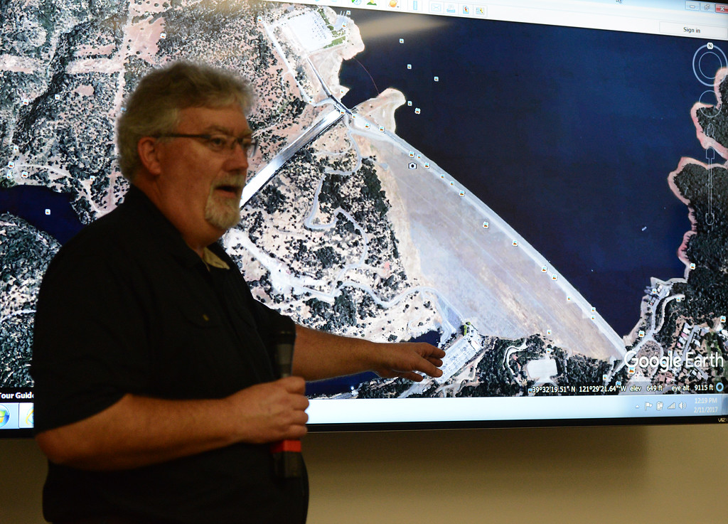 . California Department of Water Resources acting director Bill Croyle points to the Oroville Dam power plant as he talks about water flowing over the emergency spillway Saturday, Feb. 11, 2017, and in the main spillway in Oroville, California. (Dan Reidel -- Enterprise-Record)